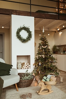 Comfortable cozy living room decorated with christmas tree with gifts, wreath frame, fireplace, sofa, plaid, carpet