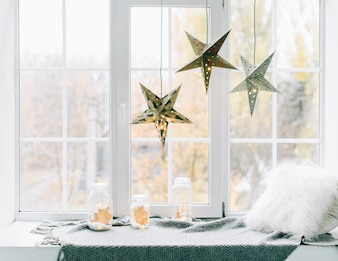 Comfortable decorated place for lying near the window. Christmas and New Year concept