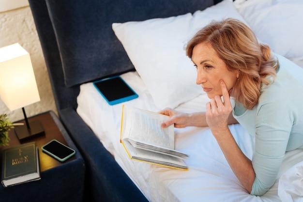 快適な国産服。ハードカバーの本と未完成のベッドで休んで、思慮深く脇を見ている貴重な明るい髪の女性