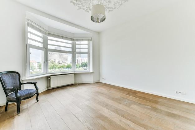 Удобное элегантное кресло на деревянном полу у окна в просторной светлой комнате дома