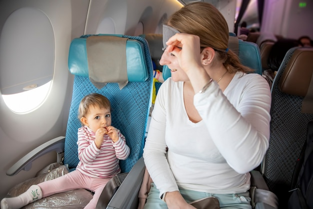 Comfortable flight cute toddler girl sit in airplane chair mother lift her sleeping mask and smile