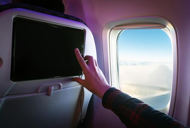 Комфортный полет на борту современного самолета. пассажир-мужчина выбирает фильмы на экране монитора, расположенного на спинке сиденья. нажимает пальцем на сенсорный экран. развлечения во время полета