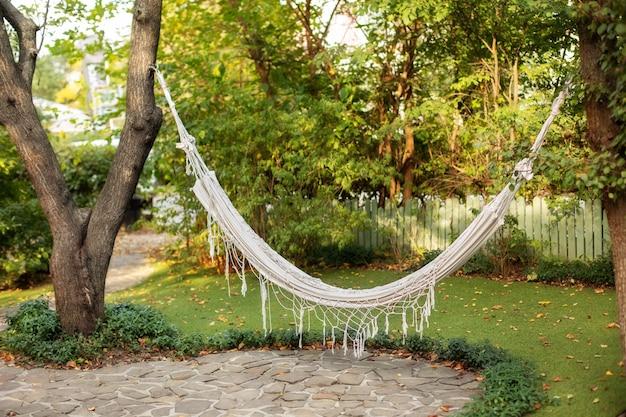 夏の庭の木にぶら下がっている快適なハンモック