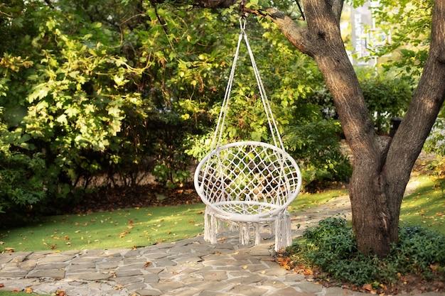 Удобное подвесное плетеное белое кресло в летнем саду