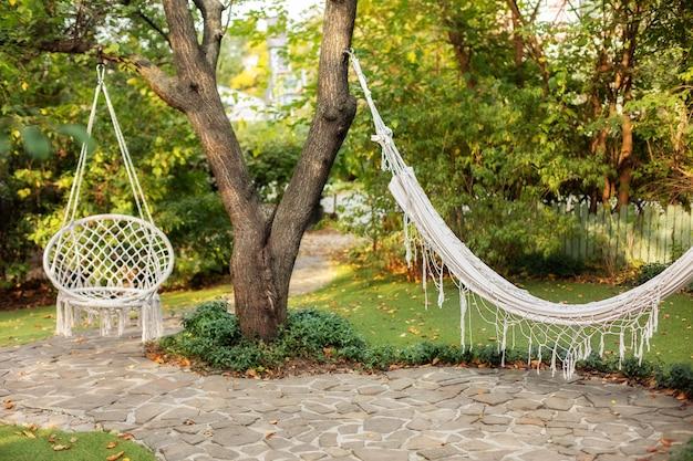 여름 정원에서 편안한 교수형 고리 버들 세공 흰색 의자