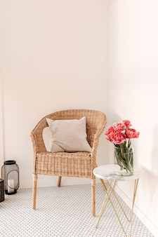 Comfortable home rest space with rattan chair, white wall, mosaic tile, marble table with beautiful peony flower bouquet, pillow