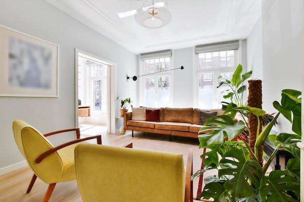 편안한 가죽 소파와 장식용 천장이있는 밝은 거실에 몬스 테라 식물이있는 화려한 안락 의자