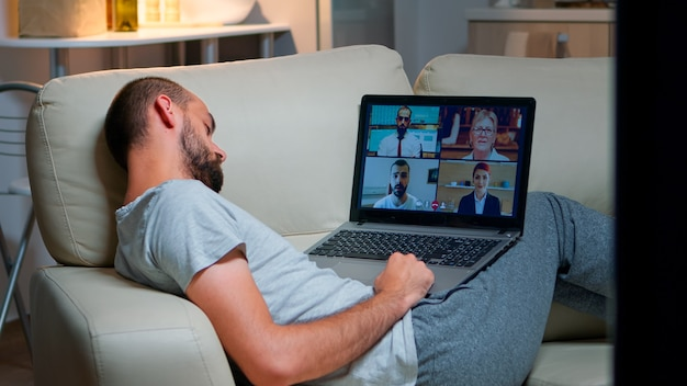 Comfortable man in pajamas falling asleep while chatting with collegues