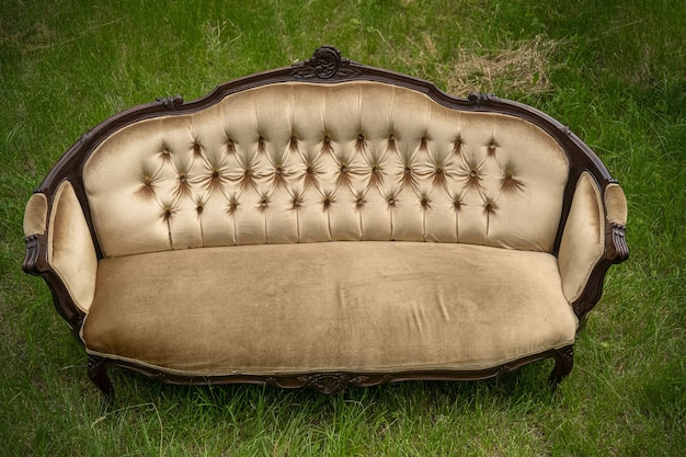 Comfortable old sofa on green lawn on summer day. luxurious vintage backyard furniture. top view. relax concept.