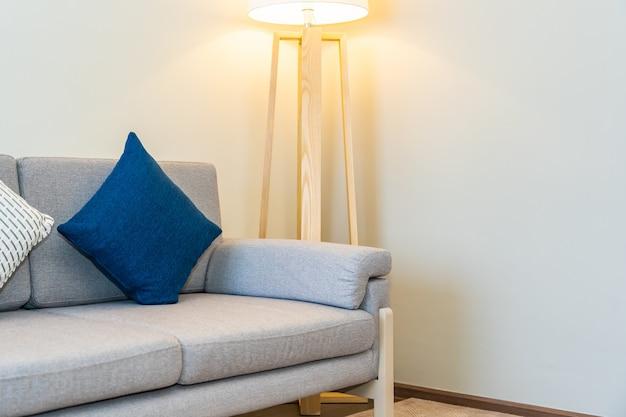 Удобная подушка на диван, украшенная светлой лампой интерьера