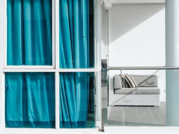 Comfortable rattan sofa bed with pillows decorated on balcony and patio on high building on white wall near blue curtain and glass door outside of the room.