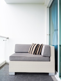 Comfortable rattan sofa bed with pillows decorated on balcony and patio on high building on white wall near glass door outside of the room