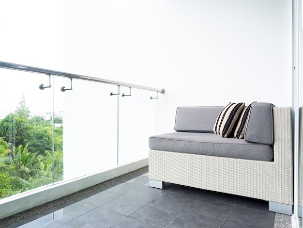 Comfortable rattan sofa bed with pillows decorated on balcony and patio on high building on white wall near glass partition outside of the room
