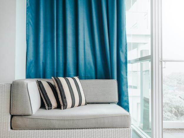 Удобный диван-кровать из ротанга с подушками, украшенными на балконе и патио на высоком здании, на синей занавеске у стеклянной двери внутри комнаты.
