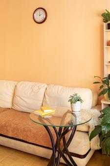 밝은 색상의 소파, 그린 하우스 식물 및 창의적인 유리 테이블이있는 편안한 휴양 공간입니다. 휴식을위한 집 진짜 아늑한 인테리어.