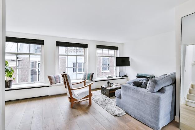 안락한 소파와 안락 의자는 현대적인 아파트의 아늑한 조명 거실 창문 근처의 부드러운 카펫 위에 놓았습니다. 프리미엄 사진