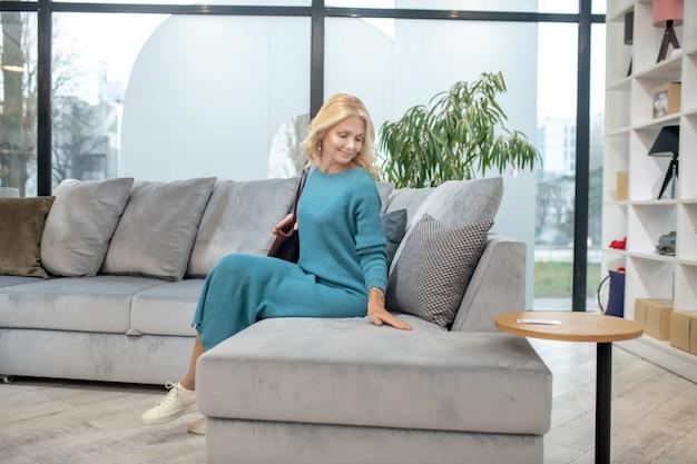 快適なソファ。家具店のラウンジにある大きな快適なソファーに座っている長いドレスを着たきれいな女性が喜んでいます。