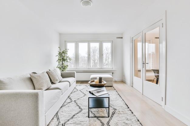 현대 아파트의 창문과 문이있는 밝은 거실의 테이블 근처 카펫에 쿠션이있는 편안한 소파