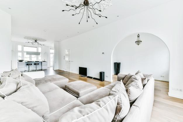 Удобный диван с мягкими подушками, расположенный под стильной люстрой в просторной светлой гостиной с аркой.
