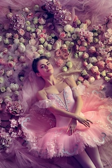 Comfortable. top view of beautiful young woman in pink ballet tutu surrounded by flowers. spring mood and tenderness in coral light.