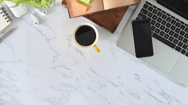 Comfortable top view laptop, smartphone, coffee, books, earphones on office desk marble table.