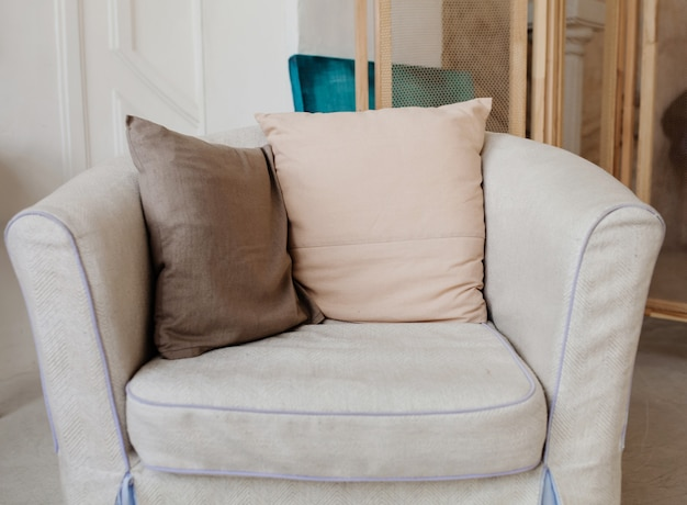 Comfortable upholstered chair with pillows in the interior of the apartment
