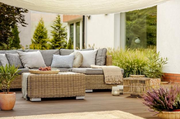 Comfortable wicker garden furniture with grey pillows in beautiful backyard