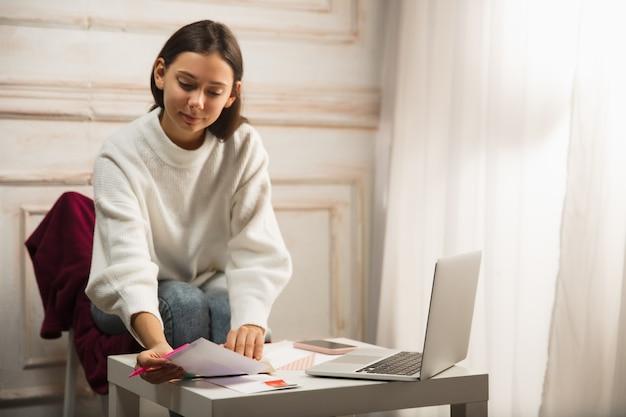 快適。ノートパソコンを持って家に座っている友人や家族のための手紙、2021年の新年とクリスマスのグリーティングカードを書く女性。休日、お祝い。陽気で、幸せで、注意深く見えます。