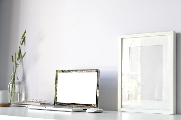 白い机のオフィステーブル上の空白の画面のラップトップコンピュータとモックアップポスターで快適な職場