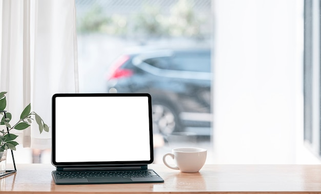Comfortable workspace at home with blank screen tablet and magic keyboard on wooden table.