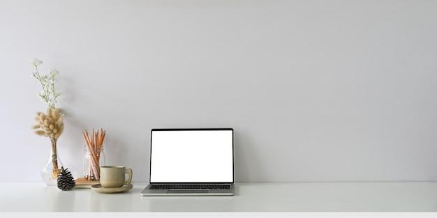 편안한 작업 공간은 흰색 빈 화면 컴퓨터 노트북 및 액세서리로 둘러싸여 있습니다.