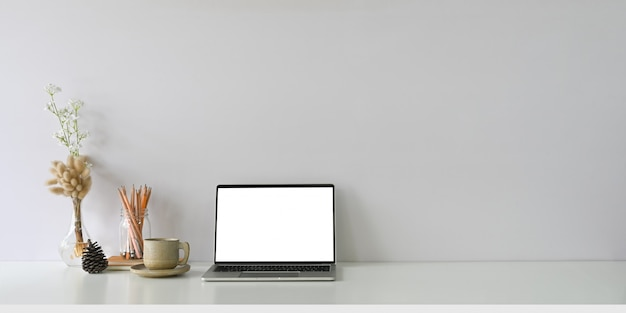 Comfortable workspace is surrounding by a white blank screen computer laptop and accessories.