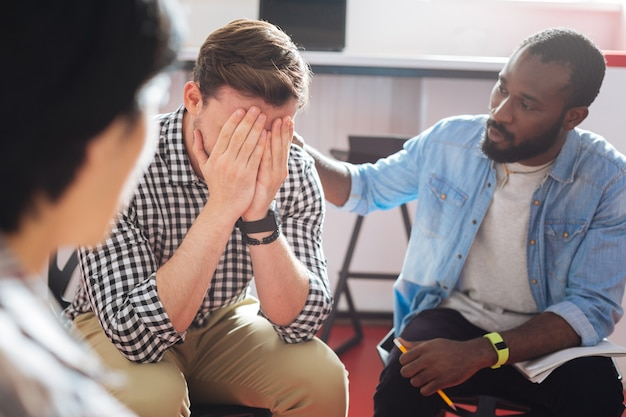 慰め。泣いている人の肩に手を置いて話している信頼できる親切な黒人男性