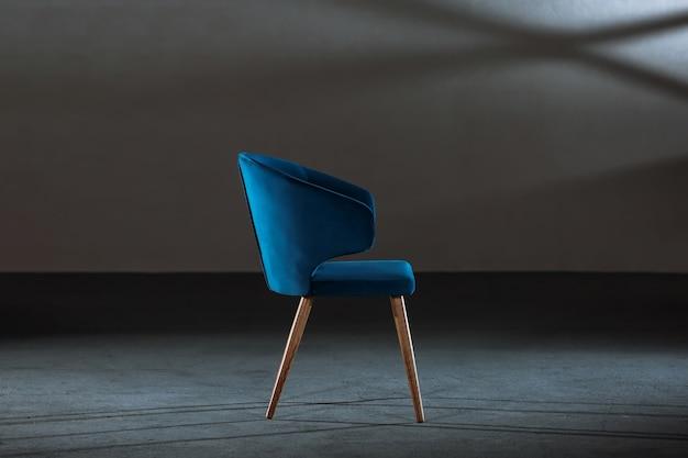 Удобное синее кресло с подлокотниками в комнате с серыми стенами