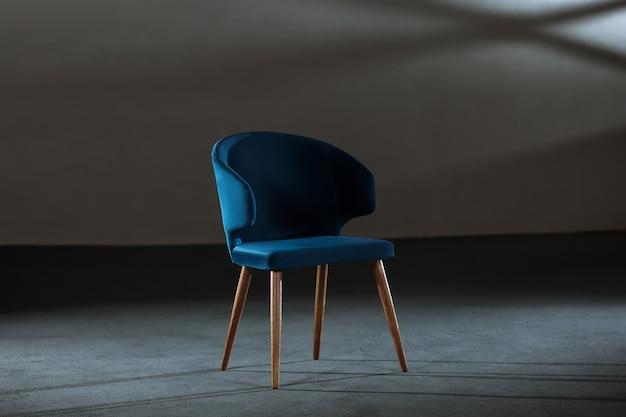 회색 벽이있는 스튜디오의 편안한 파란색 윙 의자