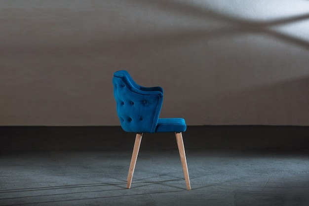 Комфортное синее кресло с подлокотниками в студии с серыми стенами