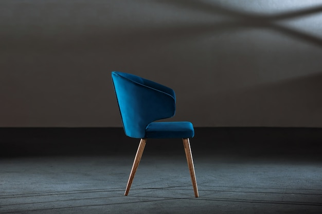 Comfy blue wing chair in a room with gray walls