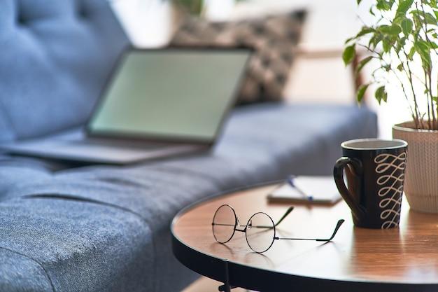 Комфортное уютное домашнее рабочее место с ноутбуком для удаленной работы в сети