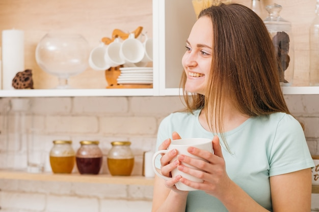 Comfy home leisure. restoring energy and relaxing. happy smiling woman enjoying tea or coffe in the kitchen.
