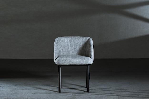 Комфортное белое кресло с подлокотниками в комнате с серой стеной