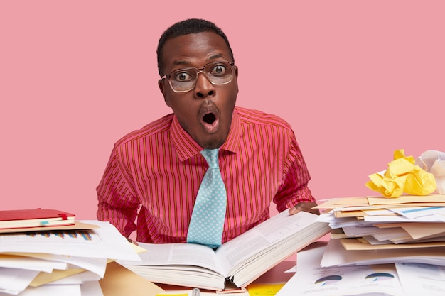 Comic horrified black male wonk holds thick opened book, stares in stupor, works on writing course paper, has pile of papers on table