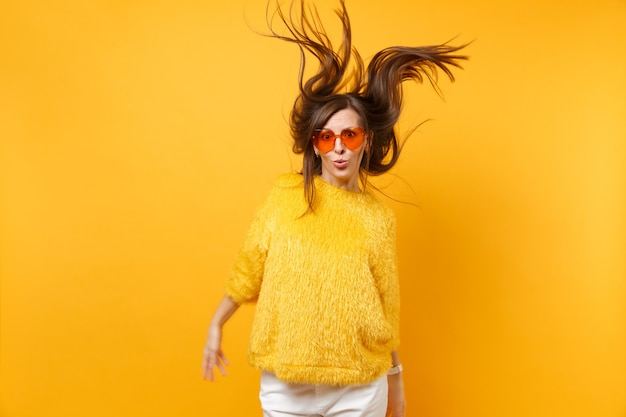 Comic young girl in fur sweater, heart orange glasses fooling around in studio jump with windy hair isolated on bright yellow background. people sincere emotions, lifestyle concept. advertising area.