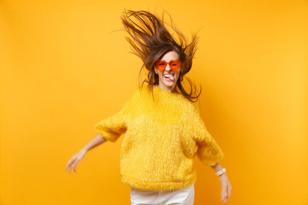 Comic young girl in fur sweater heart orange glasses showing tongue, fooling around in studio jump with flying hair isolated on yellow background. people sincere emotions, lifestyle. advertising area.