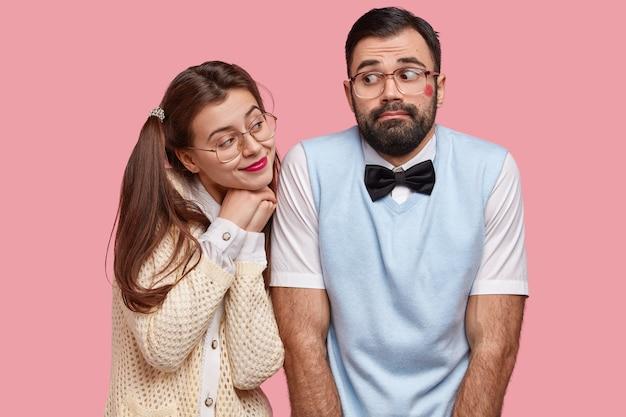 Комическая молодая женщина с двумя конскими хвостами с любовью смотрит на парня, у которого красная помада на щеке после поцелуя