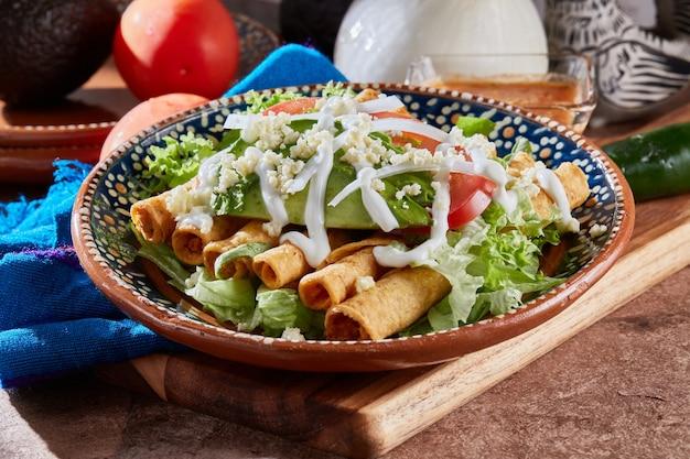 Comida mexicana tacos dorados o flautas de pollo con lechuga queso crema y tomate