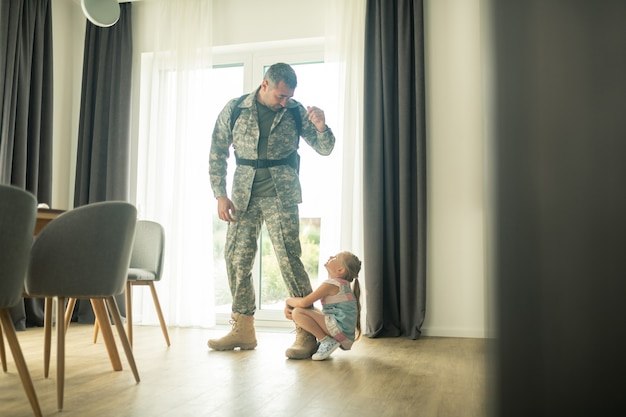 Coming back soon. loving serviceman calming his cute daughter down while coming back soon
