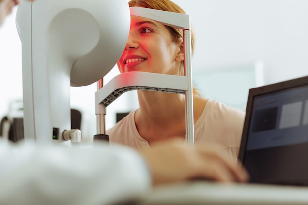 Coming for consultation. young appealing woman sitting in front of eye doctor while coming for consultation