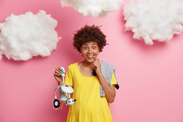 Coming maternity. positive pregnant woman in third trimester poses with mobile and bodysuit for baby, dressed in comfortable home wear, anticipates of newborn, has big tummy. child birth concept