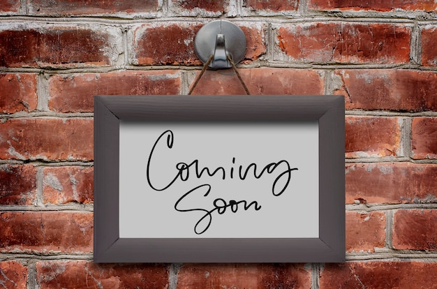 Coming soon. handwritten inscription in a wooden frame. brown brick wall.