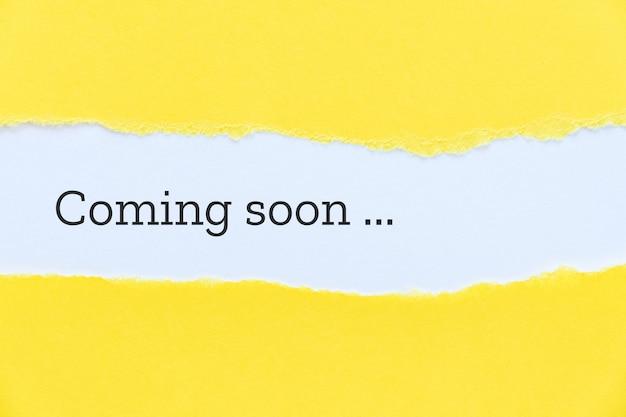 引き裂かれた黄色い紙の背景にタイプライターで書かれたすぐに来るフレーズ